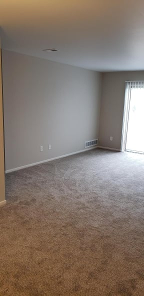 Living area with beige carpet, 2 tone paint and white doors. Door to hallway to left.
