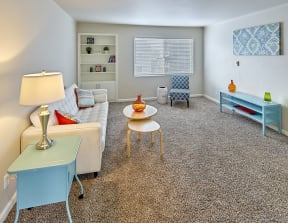 Large carpeted living space with window and staged with a couch, side tables, coffee table, chair and art.
