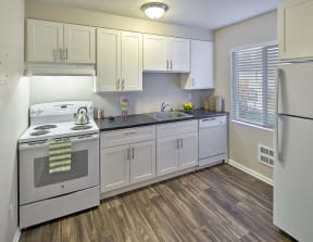 Kitchen with white cabinets and grey countertops. Image contains a white oven, sink and white dishwasher. One window and wood style flooring.