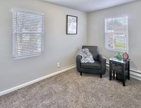 Carpeted living space, with two windows on two walls. Staged with a chair and side table.