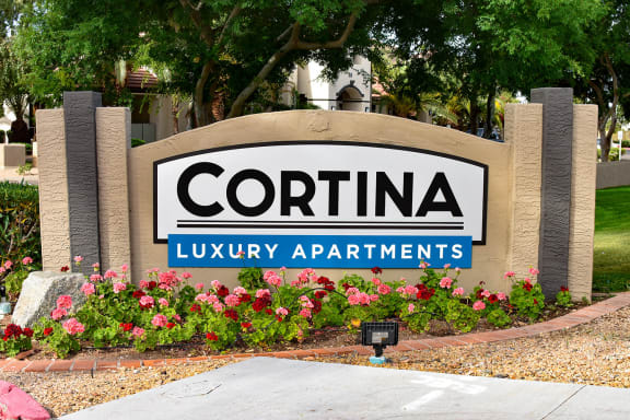 Signage reading Cortina Luxury Apartments with orange and red flowers planted in garden in front of sign