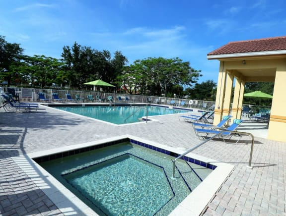 Pool area heated jacuzzi spa with lounge seatings and umbrellas