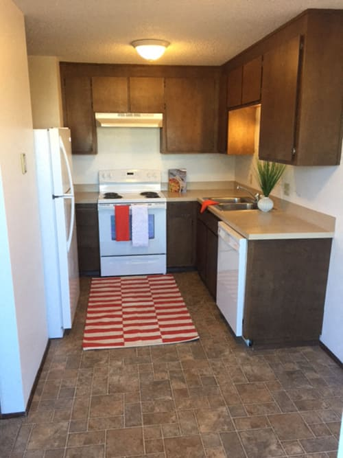 Kitchen with a sink, dishwasher, fridge, and oven with cooktop.  There are upper and lower cabinets.