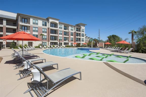 Exterior of apartments with loungers by pool