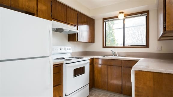 Carolyn Court   Kitchen with Wood Cabinetry and White Appliances