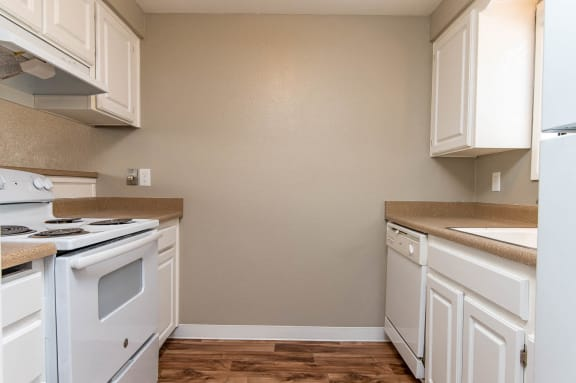 Galley style kitchen with white cabinets, white stove, hood vent and white dishwasher. Tan countertops, stove to the left, sink and dishwasher to the right.