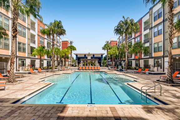 Resort-style swimming pool with lap lanes surrounded by tanning deck at EOS in Orlando, FL