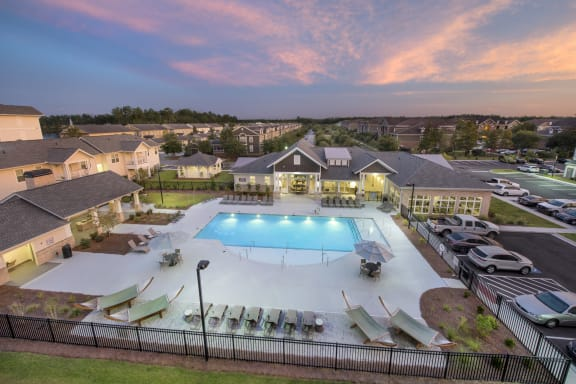 Aerial view of the Station at Savannah Quarters swimming pool, clubhouse, and community at twilight