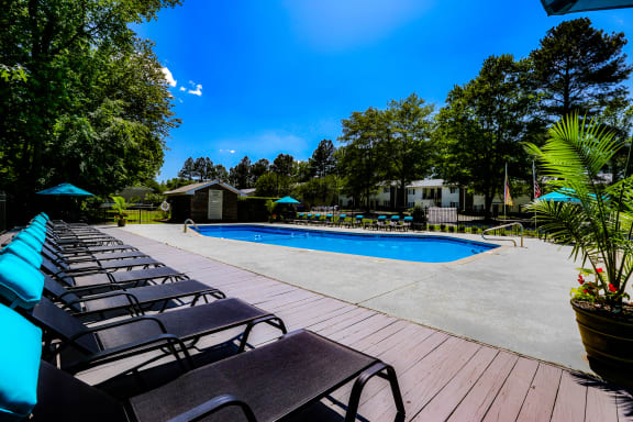 Resort-style swimming pool with lounge chairs and umbrellas at Signature Place apartments