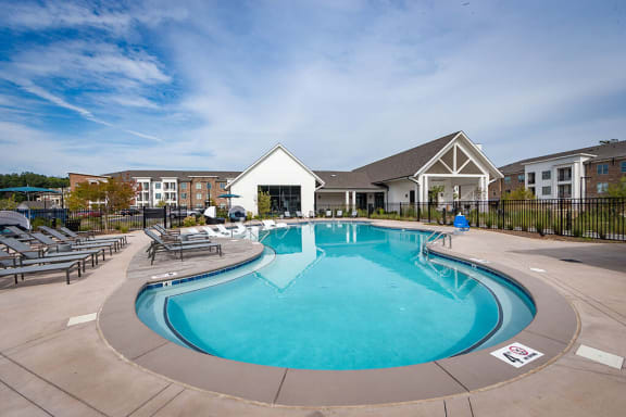 Swimming pool with large sundeck has lounge chairs at Pointe at Research Park