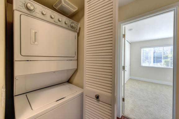 Full Sized stackable washer and dryer inside a closet with acordian style door. Washer/dryer closet location is just outside of bedroom.