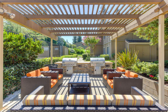 Outdoor BBQ Area with Patio, Red Cushioned Chairs, Grills, Shade, and Plants