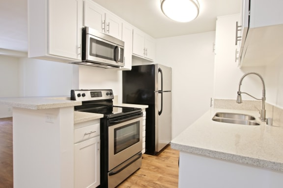 Kitchen with stainless steel 2 door refrigerator, electric stove over microwave range hood, double kitchen sink, wood style floors, white cabinets, light quartz counter tops