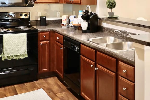 model kitchen with black appliances and wood cabinets at Centerville Manor Apartments, Virginia