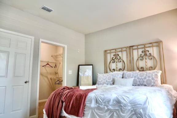 high ceiling in guest bedroom with large closet and model furniture
