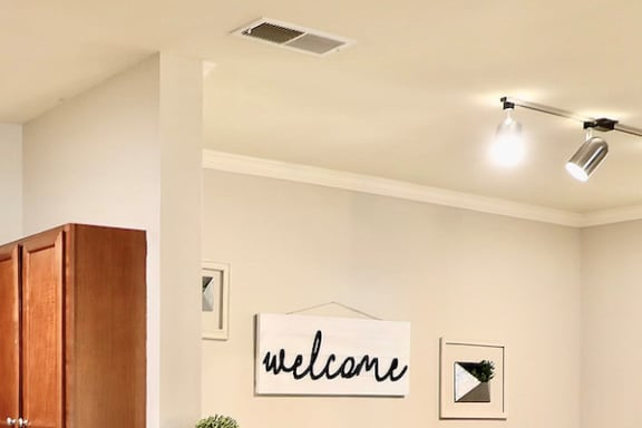 air vent in ceiling by track lighting in dining room
