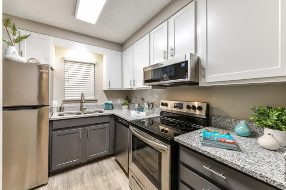 kitchen with dark lower cabinetry, white upper cabinets, and stainless steel appliances