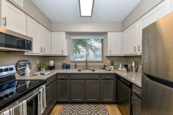 kitchen with stainless steel appliances, granite countertops, and hardwood-style flooring