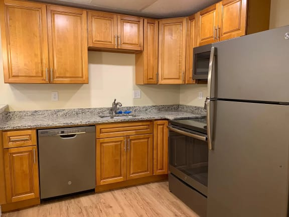 Essex Stoughton kitchen with granite countertops stainless appliances dishwasher range oven microwave