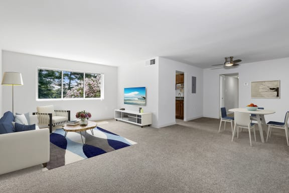 living and dining room at Overlook Apartments in Hyattsville, MD with couch, chair, coffee table, light carpeting and area rug, console table and mounted TV and white dining table seating four