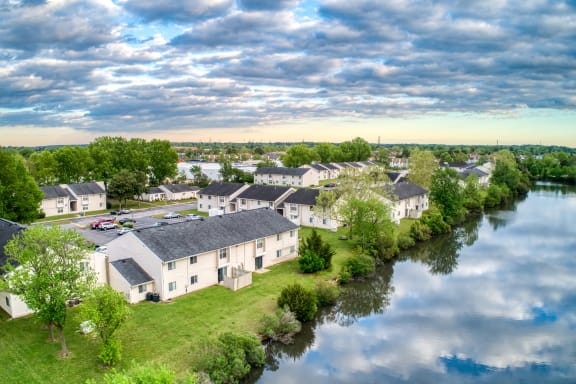 aerial view of Bridle Creek Apartments in Virginia Beach, VA with blue skies and clouds on top, grass, trees and water surrounding buildings
