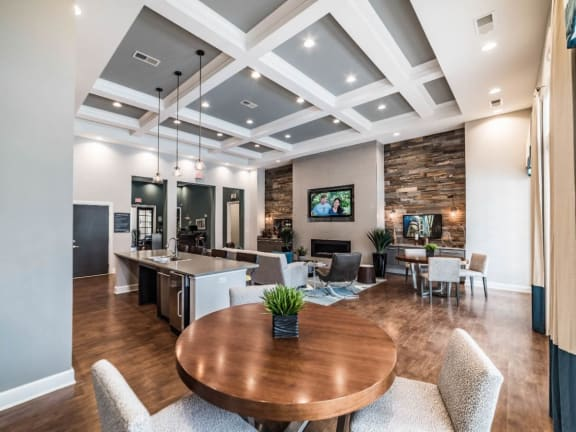 Club house, seating area, hardwood floors, Island, four chairs by island, tv, hanging light fixtures, ceiling lights, spacious room, windows, and fireplace.