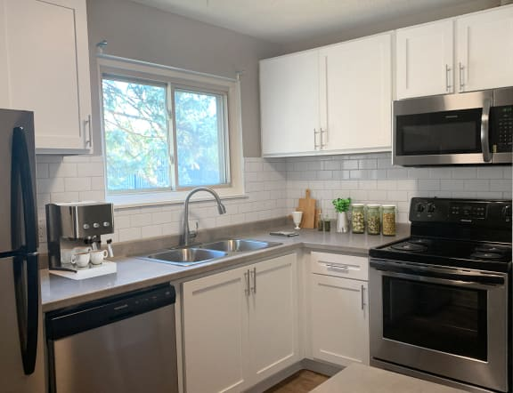 Cedarvale Elite one bedroom kitchen with stainless steel microwave, oven, dishwasher, and fridge, with elegant white cabinetry.