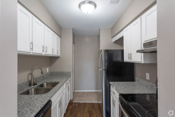 Galley-style  kitchen with granite speckled grey/white counters, white cabinets with pull handles on both lower and upper, hardwood-like flooring and stainless appliances