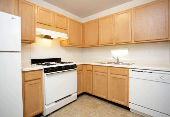 Kitchen with tan cabinets, white appliances, and tile like flooring.