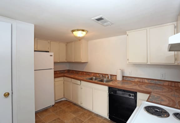 Kitchen with white cabinets, a white fridge, black dishwasher, and brown tile flooring.