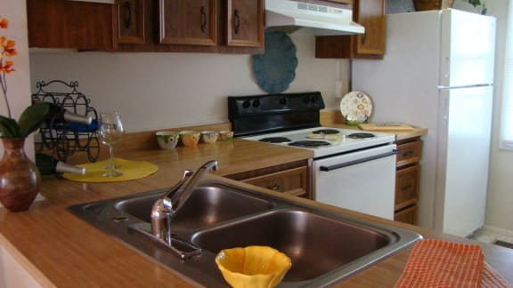 Kitchen with brown counter, brown cabinets, a stainless steal sink, and a white stove.