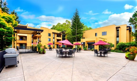 12 Central Square outdoor patio with tables, greenery and red umbrellas