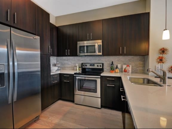 Open-Concept Kitchens with Stainless Steel Appliances, Granite Slab Countertops and Custom Cabinetry at South Park by Windsor, Los Angeles, CA 90015