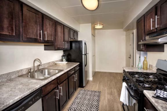 kitchen at Crestleigh apartments in Laurel MD with plank flooring, granite countertops, dark brown cabinets and stainless steel appliances