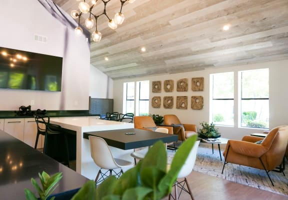 Resident lounge with a mounted big-screen TV, accent plants,tan leather chairs, coffee table, and gold framed mirrors by a window at Sorelle apartments in Moreno Valley, CA