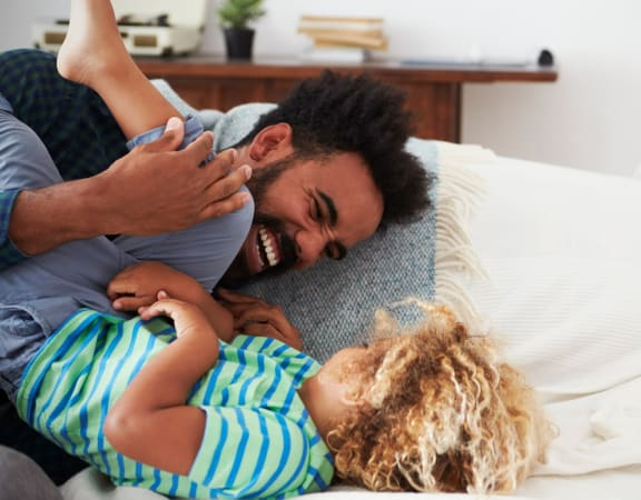 Father Smiling and Playing with Son on Couch