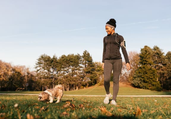 Woman in Athletic Clothing Walking Dog in Park