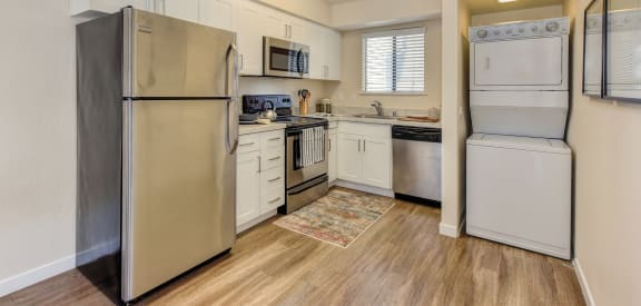 Kitchen with stainless appliances including microwave and stackable Washer & Dryer.