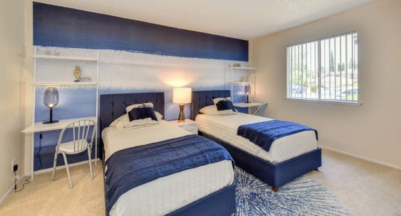 Bedroom with blue and white accent wall, Carpet, White Table with Lamp and two twin beds.