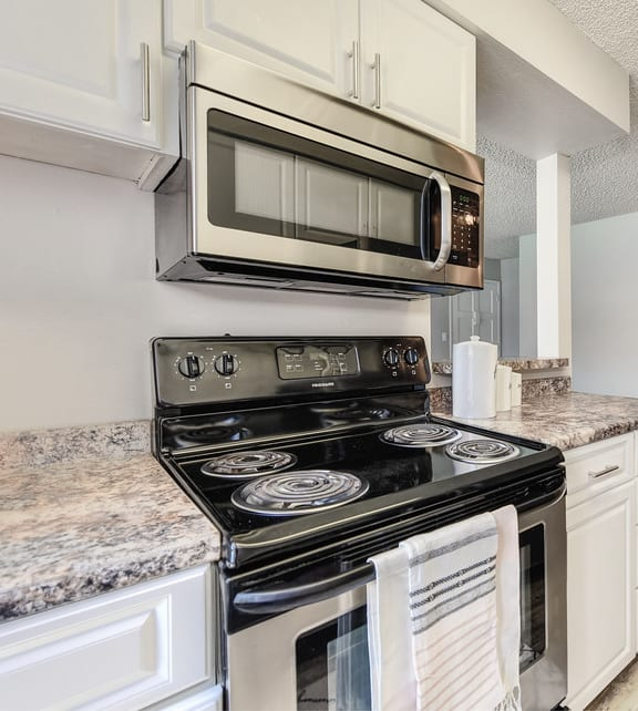 Galley style kitchen with white upper and lower cabinets. Stainless steel electric appliances. Over stove built in microwave.
