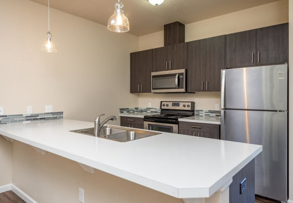 Claxter Park Apartments   Interior kitchen with white quartz countertops, stainless steel refrigerator, stove and upper microwave. Blue and grey backsplash tile. Dark lower and upper cabinetry.