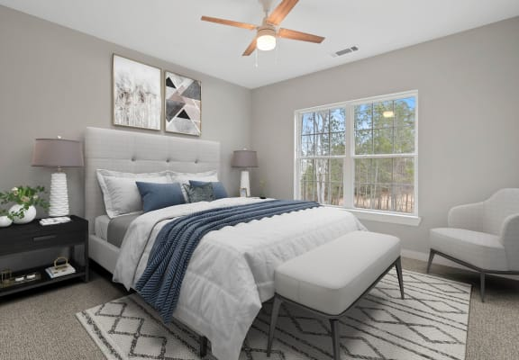 Spacious bedroom with a lighted ceiling fan and large window at 8 West in Greensboro, NC