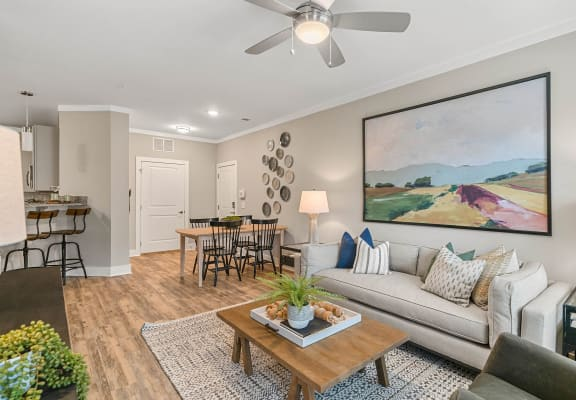 Spacious living room with plank style flooring and lighted ceiling fan at Reserve at Greenwood in Greensboro, NC