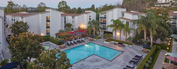 Resort-style lap pool surrounded by cabanas, string lighting and fire pits at Warner Villa, Woodland Hills, 91367