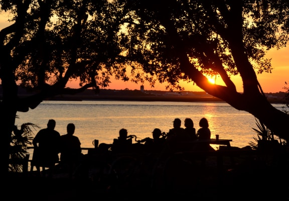 Group of friends enjoying time together under trees at the river's edge at sunset
