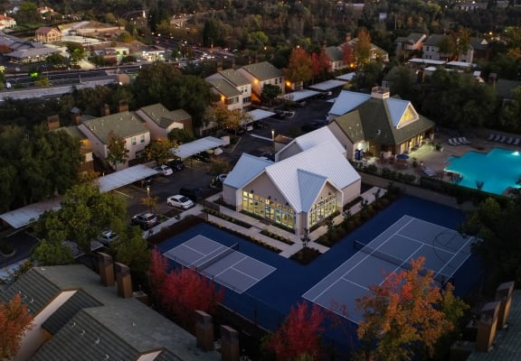 Drone Shot at Dusk showing the entire community from above. Leasing office, tennis courts and swimming pool are visible.
