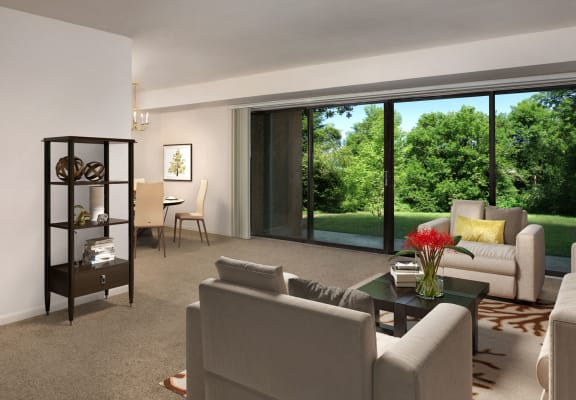 living room at Grandview apartments in Falls Church with couch and chair in the foreground and dining room area with table for four in the background