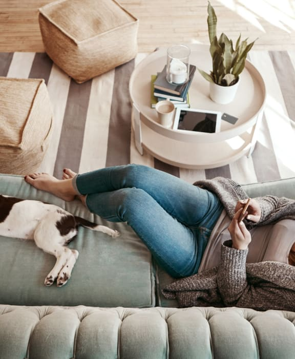 Woman Lounging on Couch with Dog at Diablo Pointe Apartments in Walnut Creek, CA 94596