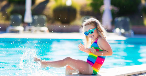 Little Girl in Sunglasses Sitting on Edge of Pool Splashing Water with Legs